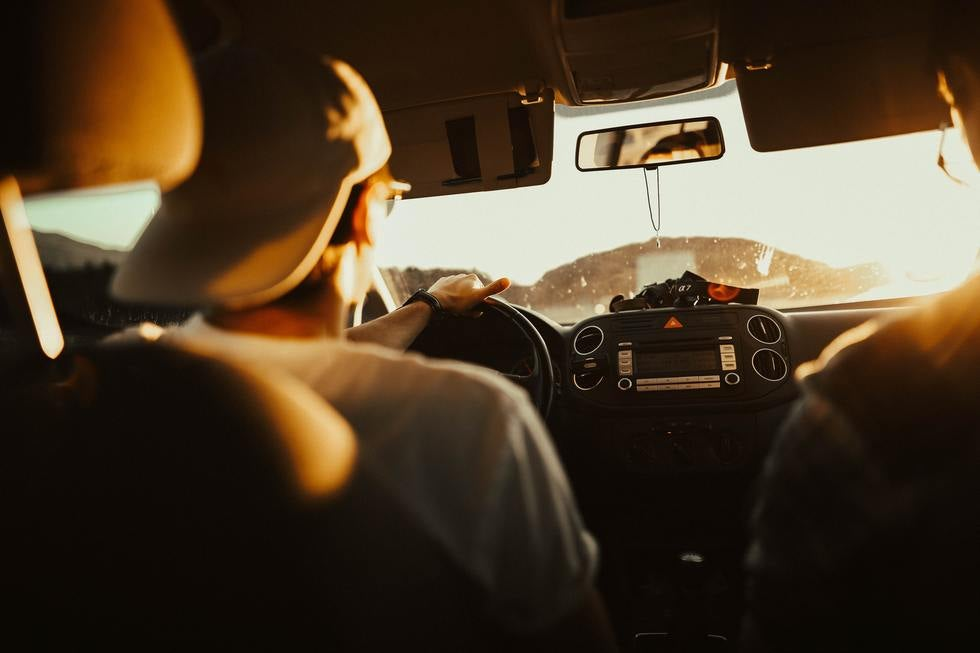 Man with backwards baseball cap driving.