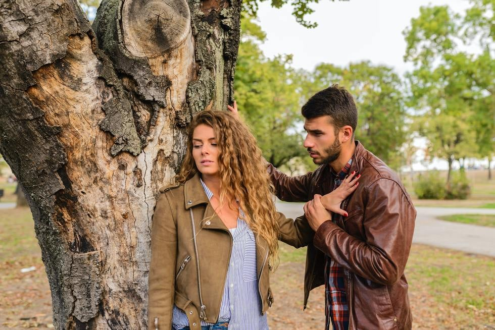 Woman pushing man away near tree.