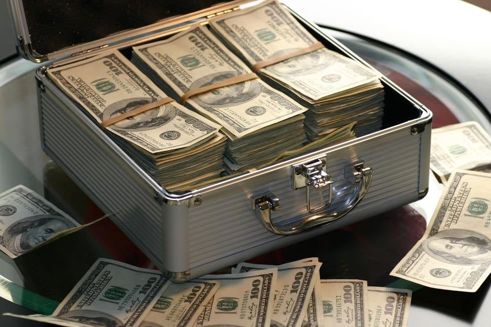 Metal box filled with stacks of hundred dollar bills.