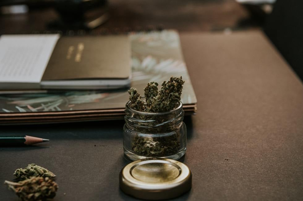 Small jar of marijuana on desk.