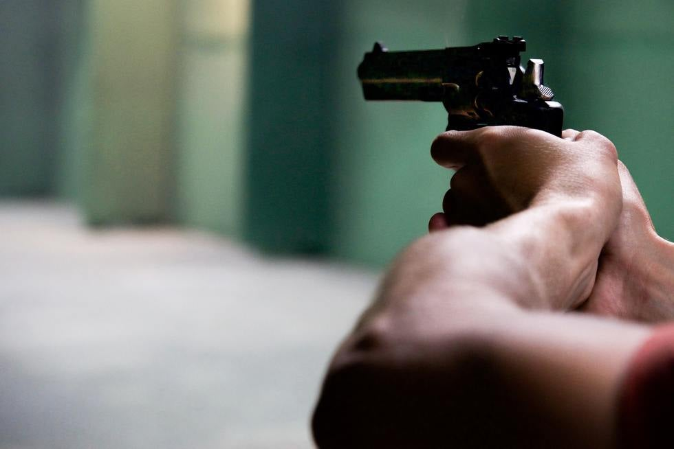 Man's arm and hand pointing gun in warehouse.