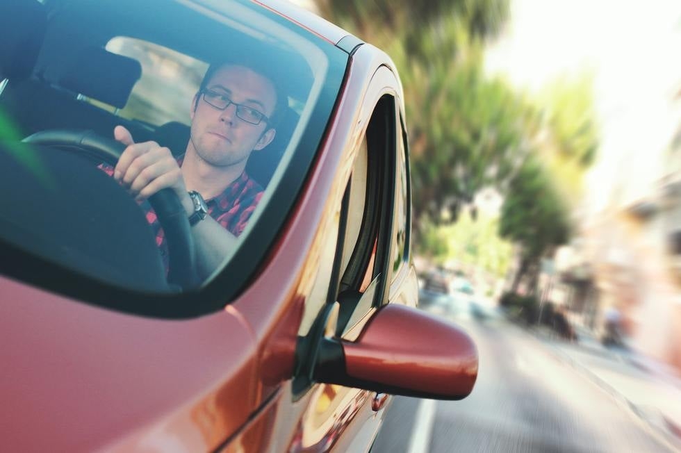 Man driving red car looking in rearview mirror.