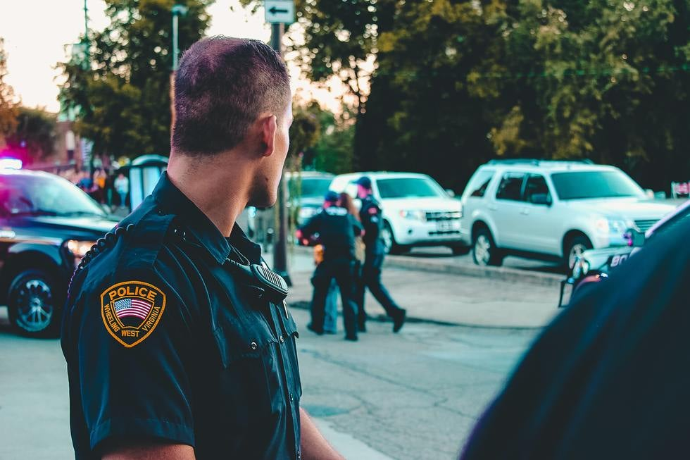 Police officers stand watching traffic.