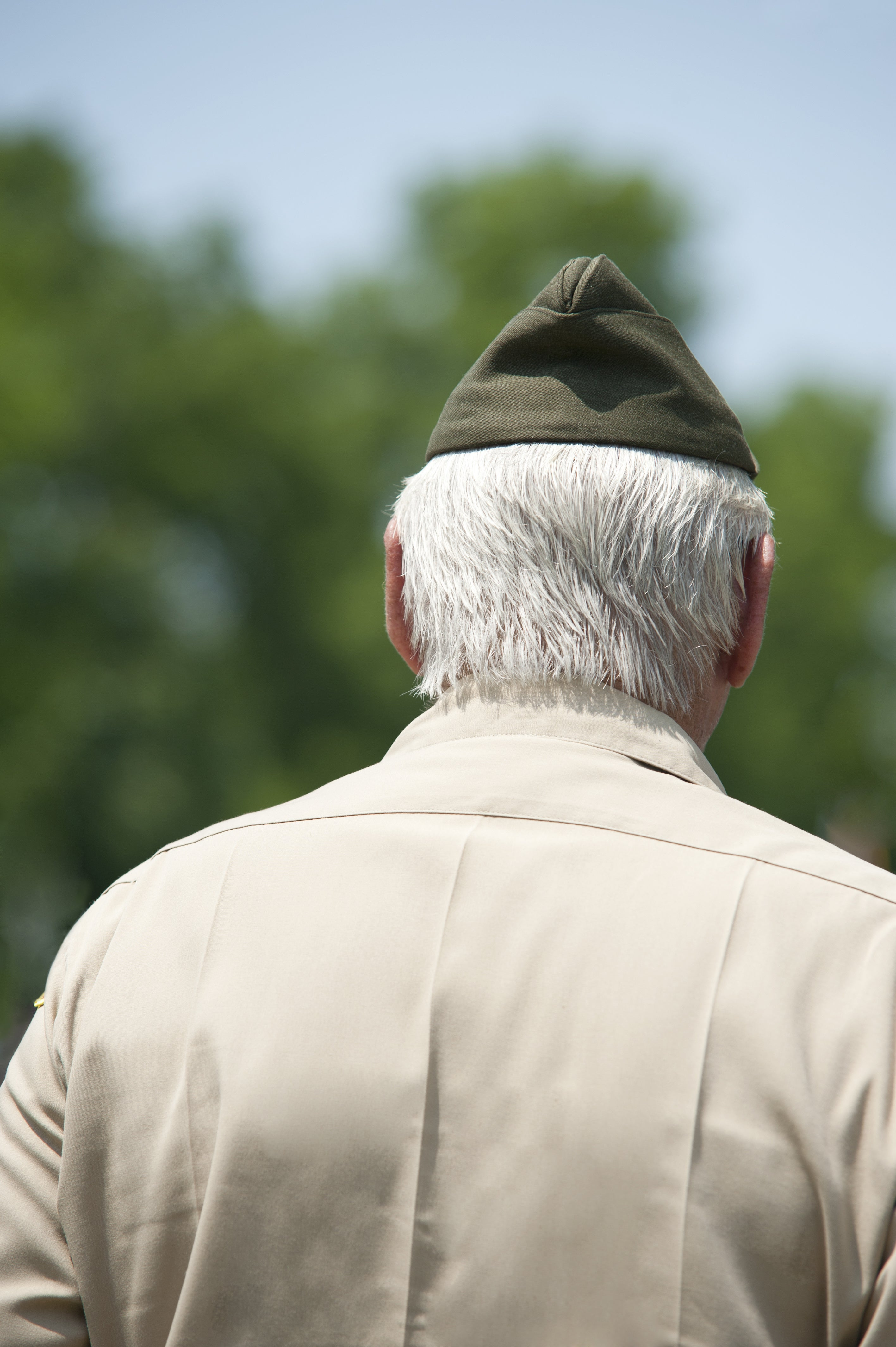 An elderly US Army Veteran at a Memorial Day Ceremony, back view with shallow depth of field