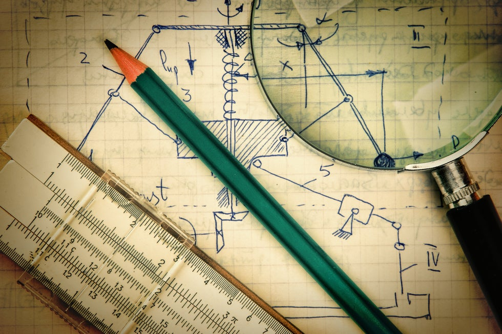 Engineering drawings with ruler pencil and magnifiying glass
