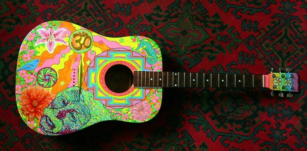Artistic guitar with colors laying on red carpet