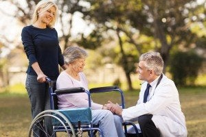 Atlanta Disability Lawyer male doctor talking with handicapped senior woman