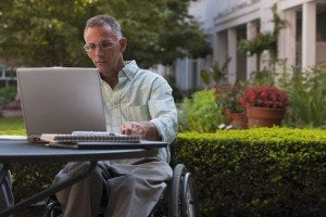 Businessman with spinal cord injury working on a laptop Decatur Social Security Disability Attorney