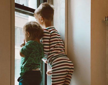 two-boys-looking-outside-window-3273852