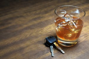 car keys next to a glass of whiskey - drunk driving (DUI)
