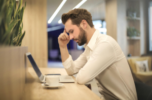 Man Pondering Over His Computer About Doing an On-Line Will.