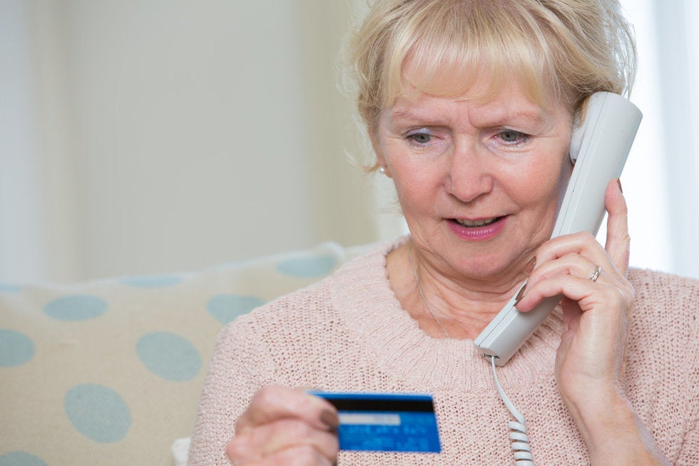 Lady giving her credit card number to a collections scammer calling on the phone.