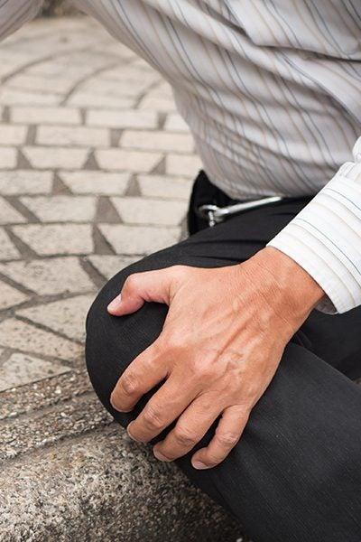 man sitting on step holding injured knee edmond ok