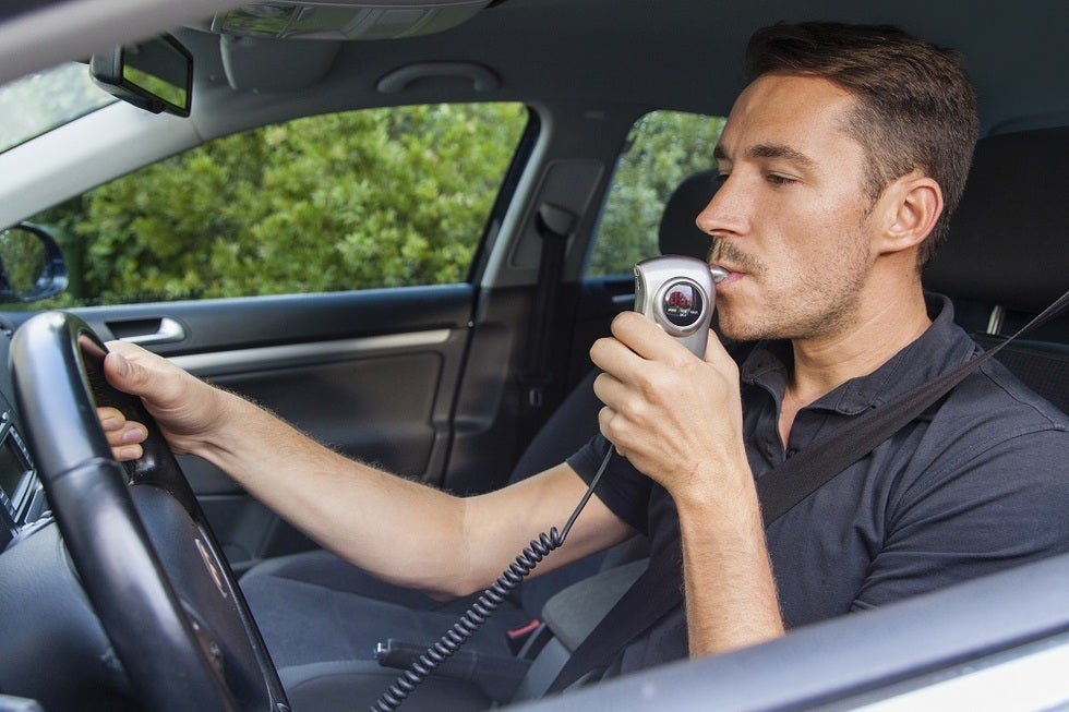 man blowing into breath test device