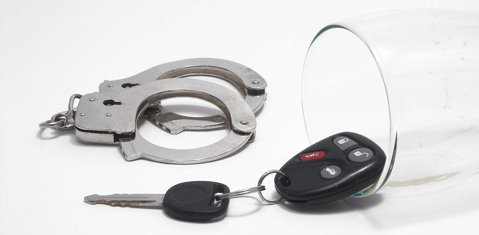 glass of liquior, handcuffs and car keys