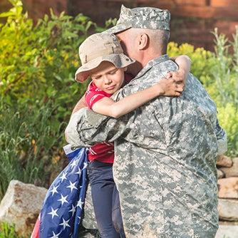 man in miltary uniform hugging child