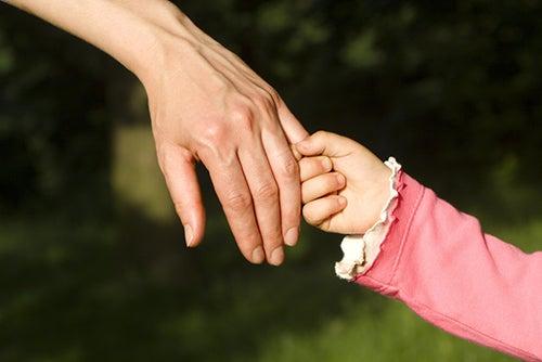 girl holding moms hand