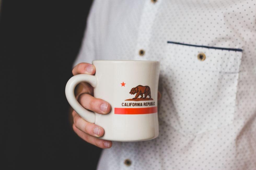Man holding mug with California Flag on mug