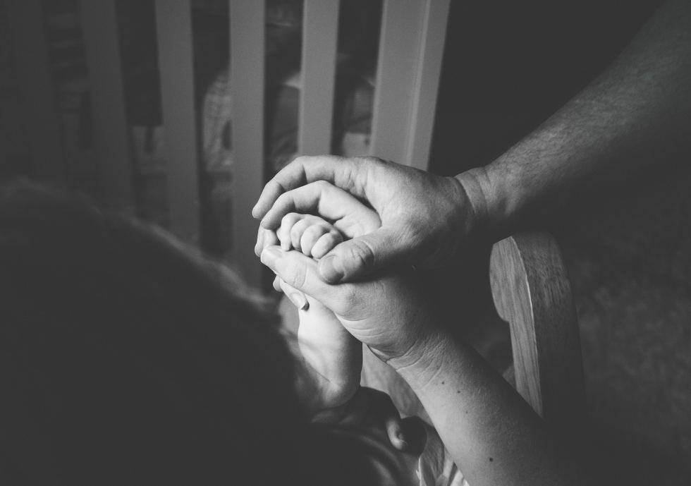 baby, man, and woman hands together