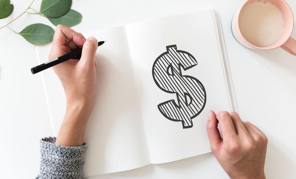hand writing money symbol in notebook