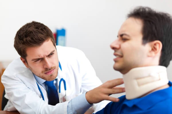 Doctor examines patient in a neck brace.