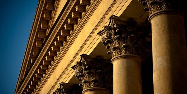 columns of a courthouse in a sunset