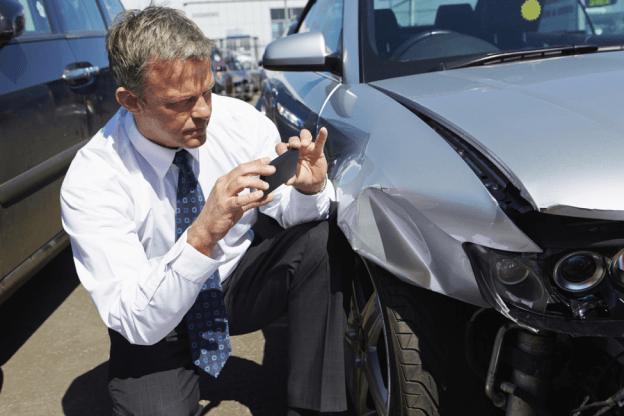 Car accident victim taking photo of car damage