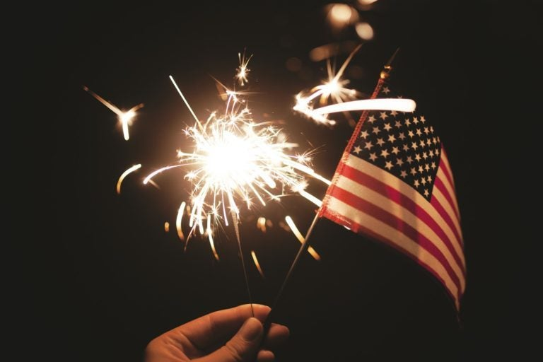 Hand holding a sparkler and small American flag.
