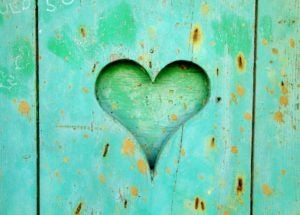 Green wooden board with a carved heart.