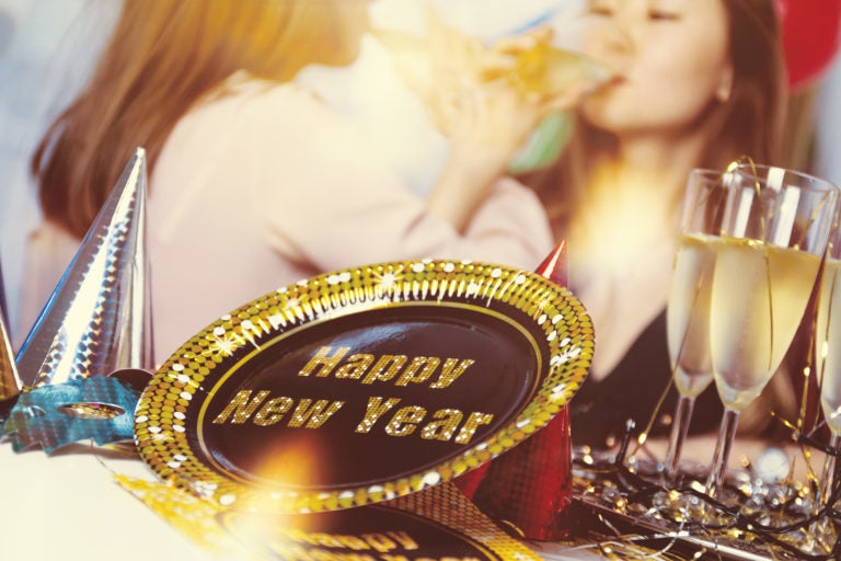 A New Year's Eve party, two women drinking, alcohol and decorations.