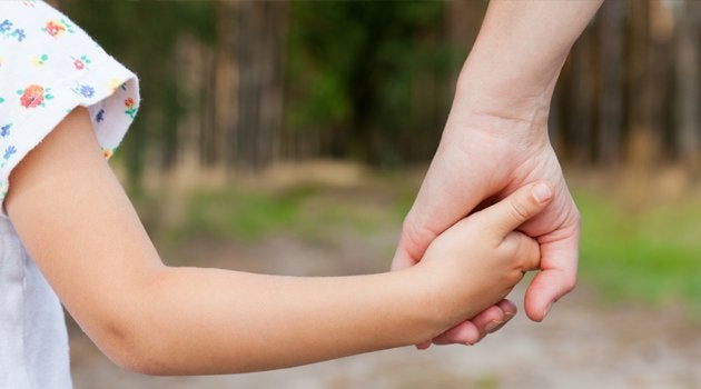 Parent holding hands with a child