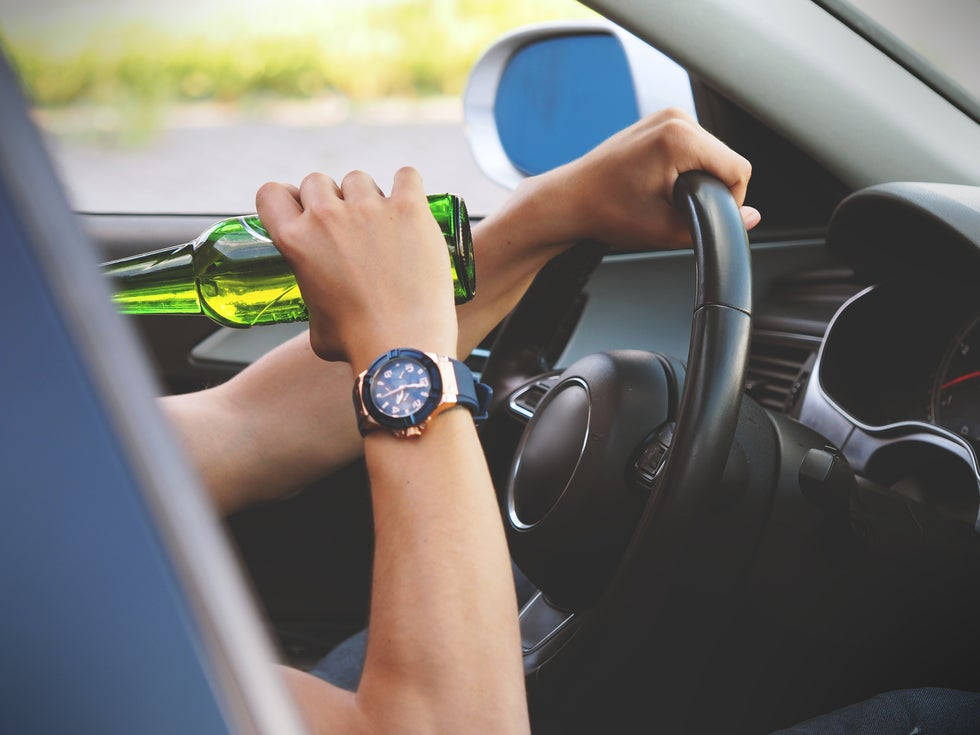 Person drinking alcohol while driving.