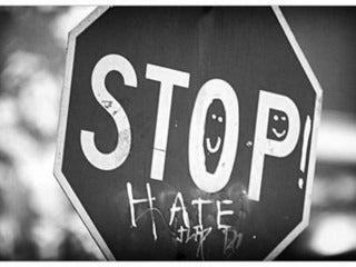 Stop sign vandalized with the word hate underneath the word stop.