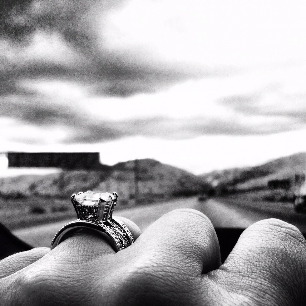 Black and white picture of hand with engagement ring.
